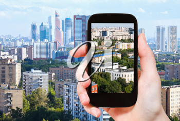 travel concept - tourist takes picture of Moscow City and urban living area in Moscow in summer afternoon on smartphone,