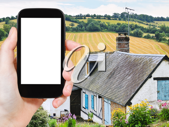 travel concept - tourist photograph peasant farm and harvested field in Normandy, France on tablet pc with cut out screen with blank place for advertising logo