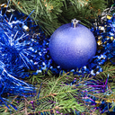 Christmas still life - one violet Christmas bauble, tinsel on Xmas tree background