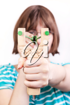 front view of girl shooting from simple wooden slingshot isolated on white background