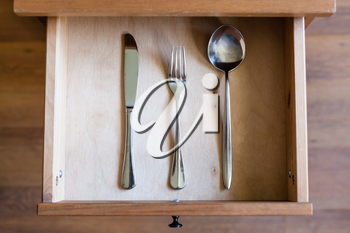 top view of knife, fork, spoon in open drawer of nightstand
