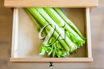 above view of green celery stalks in open drawer of nightstand