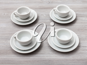 food concept - four white cups and saucers on gray brown table
