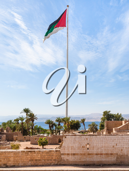 Travel to Middle East country Kingdom of Jordan - Flag of the Arab Revolt over Aqaba Fort in Aqaba city