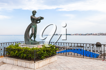 GIARDINI NAXOS, ITALY - JUNE 28, 2017: statue L' Uomo e il Mare (Man and the Sea) on waterfront in Giardini-Naxos. Giardini Naxos is seaside resort on Ionian Sea coast since the 1970s