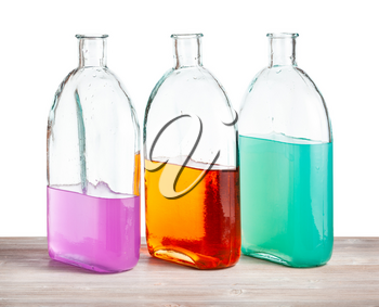 glass bottles with color watercolour solutions on wooden board with cutout background