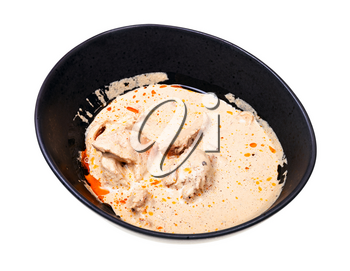 georgian cuisine - portion of Satsivi (spicy cold appetizer from chicken in walnut sauce) in black bowl isolated on white background