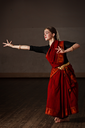 Young woman in sary dancing classical traditional indian dance Bharat Natyam