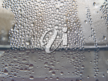 Monochrome water drops on a transparent glass surface taken closeup as background.