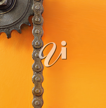 Black metal cogwheel and chain on orange background with empty space for text.
