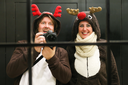 Young couple dressed up as two reindeer at Christmas in Madrid taking a selfie in an hotel mirror