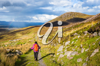 Female hiker hiking in the mountains in Ireland with rain and rainbow in the distance