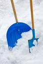Plastic and metallic blue shovels with wooden handles in the snow heap