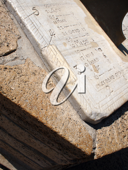 Fragment of ancient stone dial sundial closeup. On the white marble slab engraved numbers and names of the months in Russian