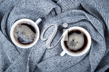 Top view of two white cups with hot coffee and gray scarf made of wool