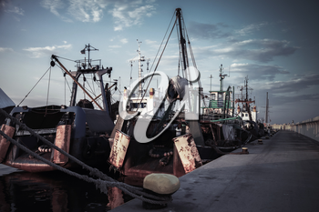 Industrial fishing boats are moored in port of Nesebar, Burgas, Bulgaria. Dark vintage tonal correction filter, retro style effect