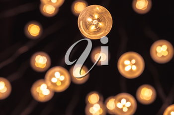Garland of bulb lamps with modern yellow LED lighting elements, close up photo with selective focus and real photo bokeh effect