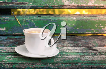 Cup of hot coffee with cream is on old wooden bench in autumn park.  Selective focus with shallow DOF