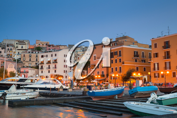 Old port with moored motorboats and yachts. Night cityscape of Gaeta town, Italy