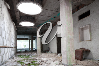 Abandoned industrial building interior. Green moss grow under round light holes in ceiling
