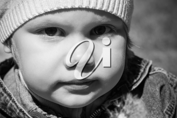 Closeup monochrome portrait of small Caucasian girl on the walk, outdoor photo