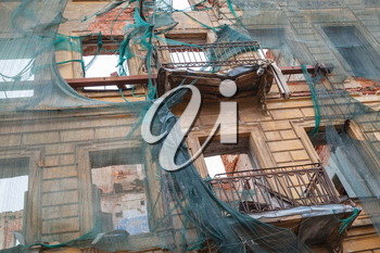 Old living house is under reconstruction, facade with broken balconies is covered with green protection mesh