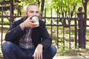 Bearded Asian man sitting on the sidewalk in park and drinking coffee from paper cup