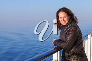 Beautiful smiling young Caucasian woman stands on the walking deck of cruise ship,  outdoor portrait