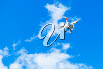 White quadrocopter in blue cloudy sky, drone controlled by wireless remote