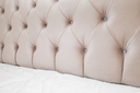 Luxury empty bedroom interior fragment, soft pink headboard and white bedding sheets on wide double bed