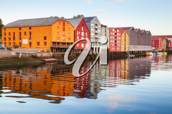 Colorful old wooden houses stand in a row along the river coast. Trondheim, Norway
