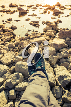 Male feet in blue canvas sport shoes standing on coastal rough rocky ground. Vertical travel lifstyle background. Vintage warm tonal correction photo filter, old style effect