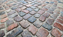 Old dark colorful shining cobblestone road background photo