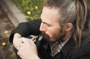 Young asian bearded man smoking pipe in summer park, close up portrait