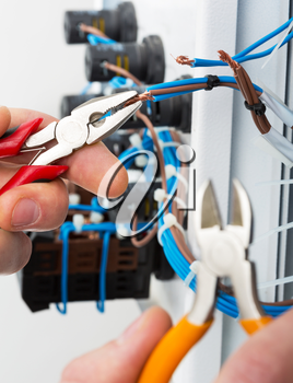 Hand of an electrician with tools at an electrical switchgear cabinet