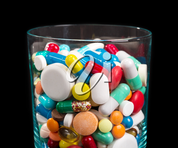 Close up of heap of many differnt pills in glass