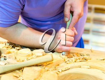 Carving tools with billets in man's hand, close up