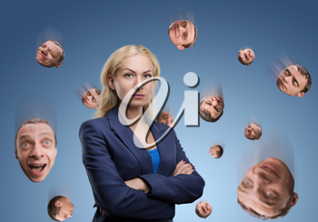 Serious businesswoman with man's head falling around