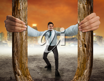 Businessman with long hands holding a big wooden horseshoe as a slingshot