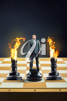 Businessman standing on the chess board instead of a pawn between two blames