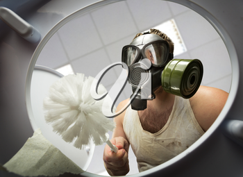 Man in gas mask with brush cleaning the toilet bowl