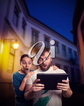 Very excited man and woman playing with tablet on the street in the evening
