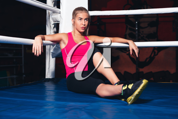 Woman sits resting in the corner of boxing ring