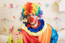 Clown in funny costume show finger. Decorative birds and nesting box on the background.
