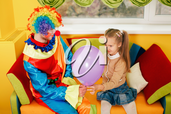 Amusing clown give air balloon to the little girl. Clown in colorful costume on birthday party.