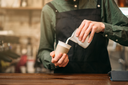 Male hands fills in a cup of milk. Blur background.
