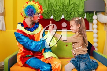 Happy little girl and  clown play palms. Decorate studio on the background.