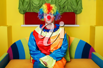 Clown in rainbow colored costume with makeup and red nose sitting on colorful sofa.