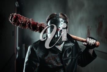Serial murderer in hockey mask holding bloody baseball-bat in hand. Wall with bloody  hand spots on background.