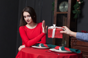 Shy woman refuses gift in restaurant. Couple relationship